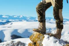 Nahaufnahme eines touristischen ` s Fußes in den Trekkingsstiefeln mit Stöcken für die gehende Stellung des Nordic auf einem Fels stockfotos