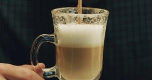 Nahaufnahme eines trinkenden Cappuccinos des Mannes von einem Stroh stock video footage
