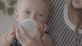 Nahaufnahme eines Trinkwassers des hübschen Babys von der kleinen Babyflasche mit der Hilfe der Mutter in der Küche Konzept von a stock video footage