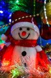 Nahaufnahme eines weißen Spielzeugschneemannes des Winters mit Weihnachtslametta im Hintergrund stockfotos