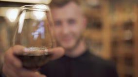 Nahaufnahme eines Weinglases, das einen hübschen Kerl hält Der Fokus bewegt sich vom Weinglas auf den attraktiven bärtigen Kerl stock video footage