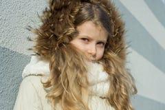 Nahaufnahme eines Winterporträts im Freien des Kindes, blondes Mädchen mit dem gelockten Haar von 7,8 Jahren in der Pelzhaube Lizenzfreie Stockfotos