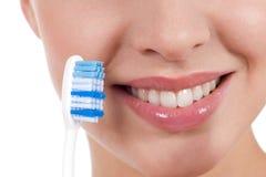 Nahaufnahme eines yougn Frauenlächelns mit Zahnbürste Stockbilder