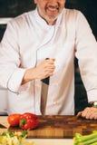 Nahaufnahme erntete Schuss des lächelnden alten Kochs, der das Messer auf dem Schneidebrett hält Stockbild