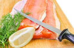 Nahaufnahme für ForellenFischfilet mit Messer auf einem Küchenbrett Lizenzfreie Stockfotos