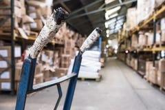 Nahaufnahme, flacher Fokus eines Griffs einer Schubkarre, benutzt, um Waren in einer Vertriebsanlage zu bewegen stockbild