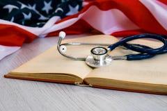 Nahaufnahme-Foto des Stethoskops und des roten Buches auf amerikanischer Flagge Medizin USA getrennte alte Bücher medizinischer G Lizenzfreie Stockfotografie