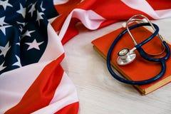 Nahaufnahme-Foto des Stethoskops und des roten Buches auf amerikanischer Flagge Medizin USA getrennte alte Bücher medizinischer G Stockbilder