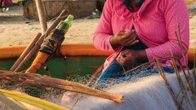 Nahaufnahme-Frau sitzt im runden Boot ausbessert Fischernetze auf Strand stock video