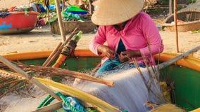 Nahaufnahme-Frau sitzt im runden Boot ausbessert Fischernetze auf Strand stock video footage