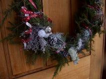 Nahaufnahme Frucht des themenorientierten Weihnachtskranzes auf einer blassen Holztür stockfoto