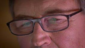 Nahaufnahme geschossen vom älteren Geschäftsmann in den Gläsern aufmerksam ernsthaft sein aufpassend und konzentriert stock video