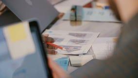 Nahaufnahme geschossen vom Entwicklungsprojektplanungsfirmenmitarbeiter, der Arbeit über Tabelle mit Bilddokumenten bespricht stock video footage