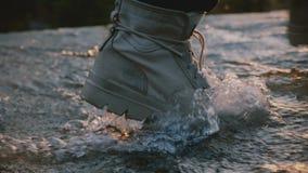 Nahaufnahme geschossen vom männlichen Bein, das den grauen wasserdichten Wüstenschuh tritt nach rechts in Wasserstrom auf Sonnenu stock footage