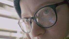 Nahaufnahme geschossen von den Frauenaugen in den Gläsern, die den Schirm eines Arbeitssmartphones reflektieren stock footage