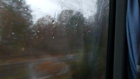 Nahaufnahme geschossen von den Regentropfen und -streifen auf dem beweglichen Bus Fensterods durch Stadtstraße im tiefen Herbst stock video footage