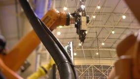 Nahaufnahme geschossen von der Bewegung des enormen automatischen Roboterarmes im Prozess auf Ausstellungshintergrund stock video