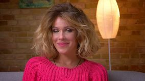 Nahaufnahme geschossen von der hübschen gewellt-haarigen Hausfrau in der rosa Strickjacke freundlich lächelnd in Kamera in der Ha stock video