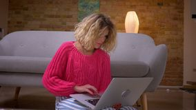 Nahaufnahme geschossen von der Hausfrau in der rosa Strickjacke, die aufmerksam in Laptop mit großer Konzentration in der Hauptat stock video