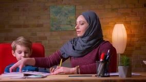 Nahaufnahme geschossen von der moslemischen Mutter im hijab Buchstaben mit ihrem kleinen Sohn zu Hause lernend auf den Tisch stock footage