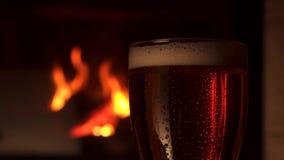 Nahaufnahme Glasbocal des Erfrischung abgekühlten Bieres mit Schaumkamin im Hintergrund stock footage