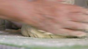Nahaufnahme, Hände einer älteren Frau kneten den Teig auf dem Küchentisch und nippen dann an Mehl auf seinem stock footage