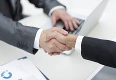 nahaufnahme Händedruck von Teilhabern über dem Schreibtisch Stockfotos