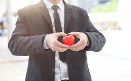 Nahaufnahme-hübscher Geschäftsmann, der ein rotes Herz gibt Lizenzfreies Stockbild