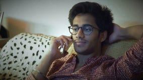 Nahaufnahme, hübscher indischer Mann in den Gläsern sprechend am Telefon, das auf Sofa And Wearing His Hair mit Verstand sitzt stock video