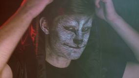 Nahaufnahme, hübscher Kerl in Chen-Haube mit dem Tier ` s Make-up auf dem Gesicht hebt den Kopf und entfernt die Haube in stock video footage