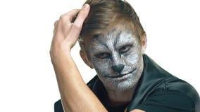 Nahaufnahme, hübscher Kerl mit dem Wolf, der auf Gesicht grimmig ist, hält Haar eigenhändig stock footage