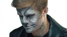 Nahaufnahme, hübscher Kerl mit Wolfmake-up auf Gesicht dreht Kopf und schaut vorwärts stock video footage