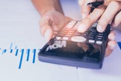 Nahaufnahme Hand des Gesch?fts- oder Kontoarbeitstaschenrechners, Gewinn oder Diagrammwirtschaft auf Hauptb?rotisch lizenzfreie stockbilder