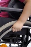 Nahaufnahme an Hand des Kindes im Rollstuhl Lizenzfreie Stockbilder