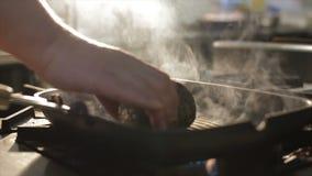 Nahaufnahme-Hand dreht Fleisch-Klumpen zu anderer Seite auf Pan stock footage