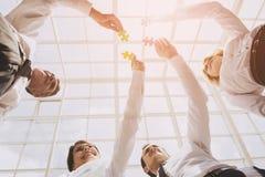 Nahaufnahme-Hand von den Leuten, die Puzzlen anschließen lizenzfreie stockfotografie