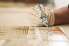 Nahaufnahme handcraft Arbeitskrafthand unter Verwendung des Malereiwerkzeugs für das Glas, welches die Farbverzierung anwendet Lizenzfreie Stockfotografie