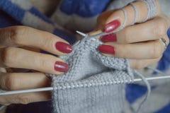 Nahaufnahme Handdes strickens Frau, die kleine Socken strickt stockbild