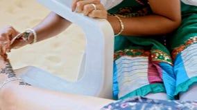 Nahaufnahme-indische Frau zeichnet Henna Tattoo auf Mädchen-Fuß stock video