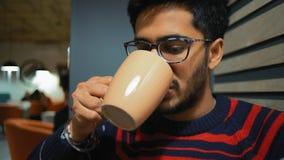 Nahaufnahme, indischer Kerl in einer warmen Strickjacke schreibt eine Mitteilung auf einen Smartphone und einen Getränkkaffee stock video
