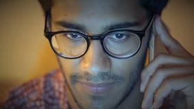 Nahaufnahme, indischer Mann in den Gläsern spricht am Telefon, das hinter dem Computer sitzt und bespricht Geschäfts-Fragen stock video footage