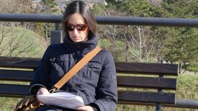 Nahaufnahme: Junge Frau, die auf einer Bank sitzt und im Park liest Petrovaradin-Festung, Novi Sad, Serbien stock video
