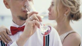 Nahaufnahme, Jungvermählten trinken Champagner im Freien, stilvollen jungen Bräutigam in den Hosenträgern und rote Fliege, blonde stock footage