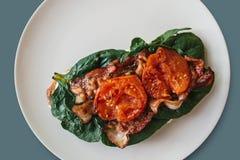 Nahaufnahme Köstlicher und nahrhafter Toast oder ein Sandwich mit Speck, Spinat und Tomaten auf einem grauen Hintergrund Geschmac Stockfotos