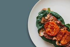 Nahaufnahme Köstlicher und nahrhafter Toast oder ein Sandwich mit Speck, Spinat und Tomaten auf einem grauen Hintergrund Geschmac Lizenzfreie Stockbilder