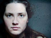Nahaufnahme-künstlerisches Porträt der kaukasischen Frau schauend durch die Frau, die durch Glas mit Wasser-Tropfen und Rissen sc Stockfotos