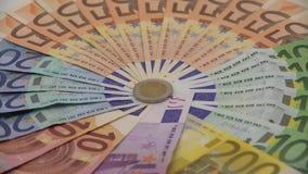 Nahaufnahme 4K der Münze zwei Euros mit Banknoten von verschiedenen Werten Kassieren Sie Geld stock video footage