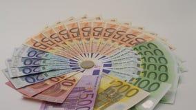 Nahaufnahme 4K einer Münze ein Euro mit Banknoten von verschiedenen Werten Kassieren Sie Geld stock footage