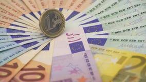 Nahaufnahme 4K einer Münze ein Euro mit Banknoten von verschiedenen Werten Kassieren Sie Geld stock video