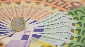 Nahaufnahme 4K einer Münze ein Euro mit Banknoten von verschiedenen Werten Kassieren Sie Geld stock video footage